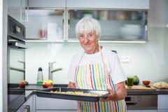 Femme supérieure faisant cuire dans la cuisine Photographie stock