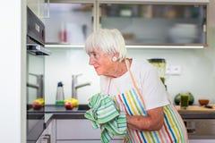 Femme supérieure faisant cuire dans la cuisine Photographie stock libre de droits