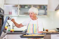 Femme supérieure faisant cuire dans la cuisine Image stock