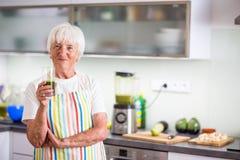 Femme supérieure faisant cuire dans la cuisine - mangeant et faisant cuire sain Images libres de droits
