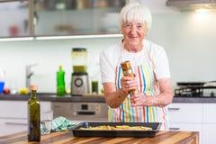 Femme supérieure faisant cuire dans la cuisine - mangeant et faisant cuire sain Images stock