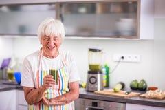 Femme supérieure faisant cuire dans la cuisine - mangeant et faisant cuire sain Photographie stock