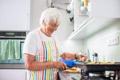 Femme supérieure faisant cuire dans la cuisine - mangeant et faisant cuire sain Image stock