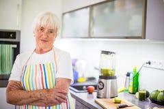 Femme supérieure faisant cuire dans la cuisine - mangeant et faisant cuire sain Photo libre de droits
