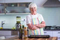 Femme supérieure faisant cuire dans la cuisine - mangeant et faisant cuire sain Image libre de droits
