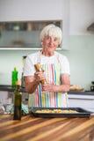 Femme supérieure faisant cuire dans la cuisine - mangeant et faisant cuire sain Photos stock