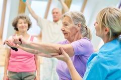 Femme supérieure faisant l'exercice avec la bande élastique image libre de droits