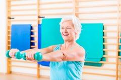 Femme supérieure faisant le sport de forme physique dans le gymnase photographie stock