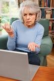 Femme supérieure frustrante à l'aide de l'ordinateur portable Photo stock