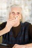 Femme supérieure fumant une cigarette Images stock