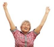 Femme supérieure gaie faisant des gestes la victoire sur un fond blanc Images stock