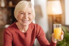 Femme supérieure gaie posant avec un verre de jus Photographie stock libre de droits