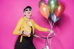 Femme supérieure gaie utilisant la veste en cuir jaune et les lunettes de soleil se tenant avec la bicyclette et les ballons Photo stock