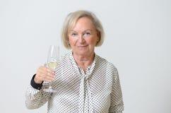 Femme supérieure grillant avec le champagne Photo stock