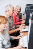 Femme supérieure heureuse à l'aide de l'ordinateur dans la classe Photographie stock libre de droits