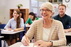 Femme supérieure heureuse à une classe d'éducation des adultes recherchant photographie stock
