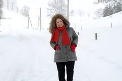 Femme supérieure heureuse amicale se tenant dans la neige Images libres de droits