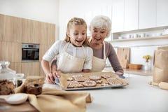 Femme supérieure heureuse appréciant le procédé de boulangerie avec sa petite-fille Photo libre de droits