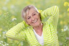 Femme supérieure heureuse avec des bras derrière sa tête en nature Photographie stock