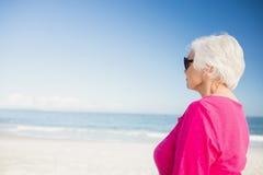 Femme supérieure heureuse avec des lunettes de soleil regardant l'eau Photos stock