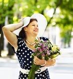 Femme supérieure heureuse avec la fleur. Photo libre de droits