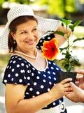 Femme supérieure heureuse avec la fleur. Images stock