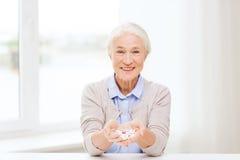 Femme supérieure heureuse avec la médecine à la maison Image libre de droits