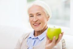 Femme supérieure heureuse avec la pomme verte à la maison Photos libres de droits