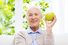 Femme supérieure heureuse avec la pomme verte à la maison Images stock