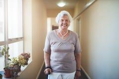 Femme supérieure heureuse avec le bâton de marche se tenant à la maison Image stock