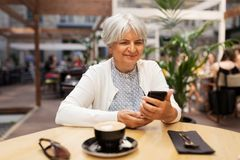 Femme supérieure heureuse avec le smartphone au café de rue images libres de droits