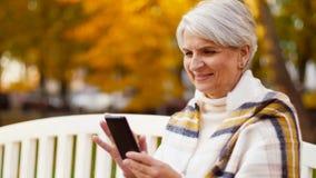 Femme supérieure heureuse avec le smartphone au parc d'automne banque de vidéos
