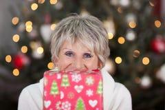 Femme supérieure heureuse avec un cadeau de Noël Photographie stock libre de droits