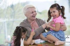 Femme supérieure heureuse ayant le temps de qualité avec des petite-filles à la maison Photos libres de droits