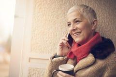 Femme supérieure heureuse ayant un appel téléphonique agréable Images stock