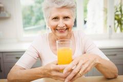 Femme supérieure heureuse ayant un verre de jus Images stock