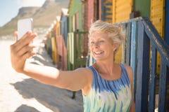Femme supérieure heureuse cliquant sur le selfie tout en se tenant contre la hutte de plage Photographie stock libre de droits