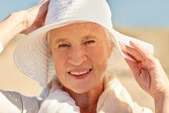 Femme supérieure heureuse dans le chapeau du soleil sur la plage d'été Photo stock