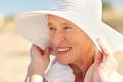 Femme supérieure heureuse dans le chapeau du soleil sur la plage d'été Images libres de droits