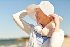 Femme supérieure heureuse dans le chapeau du soleil sur la plage d'été Photographie stock