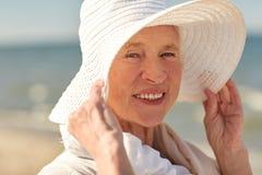 Femme supérieure heureuse dans le chapeau du soleil sur la plage d'été Image libre de droits