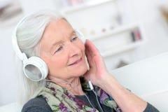 Femme supérieure heureuse de portrait appréciant la musique avec l'écouteur Images stock