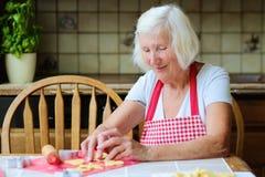 Femme supérieure heureuse faisant des biscuits à la cuisine Photo stock