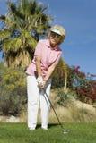 Femme supérieure heureuse jouant au golf Photos libres de droits