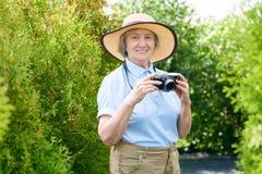 Femme supérieure heureuse prenant des photos des vacances photos libres de droits