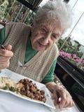 Femme supérieure heureuse prenant le déjeuner dans un restaurant Photo stock