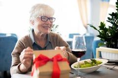 Femme supérieure heureuse recevant des cadeaux image stock