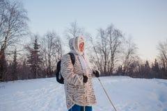 Femme supérieure heureuse regardant au coucher du soleil d'hiver dans l'activité de marche nordique de forêt Photographie stock