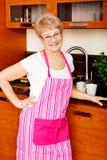 Femme supérieure heureuse se tenant dans la cuisine Photos stock