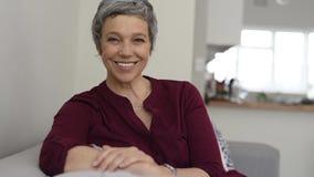 Femme supérieure heureuse souriant sur le divan banque de vidéos